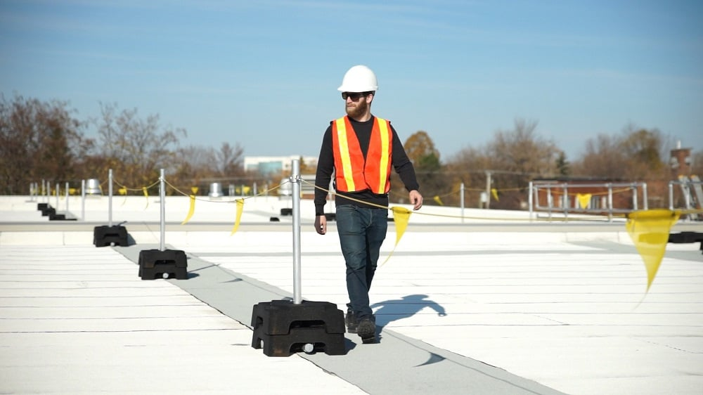 Man walking along edge of roof protected by warning line