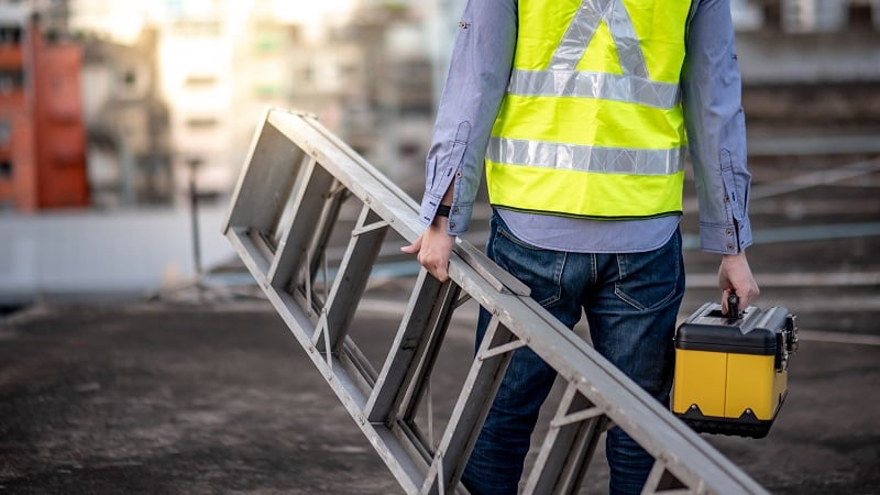 Maintenance worker holding ladder with safety clothing